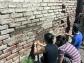 Arreglando una pared de ladrillos con mortero de barro en el Taller de Eco-Construcción Urbana en Casona Dadá.