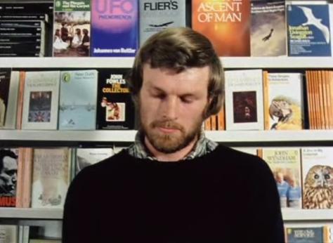 Un sereno hombre joven en una librería (o biblioteca) dedicada a los pájaros y al vuelo.